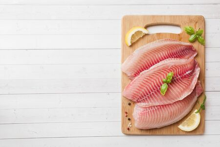 Raw fish fillet of tilapia on a cutting Board with lemon and spices. White table with copy space