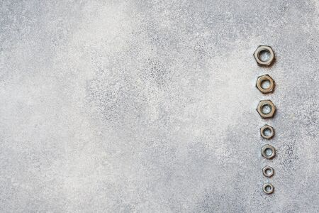 Wrenches, tools bolts and nuts on grey concrete background with copy space