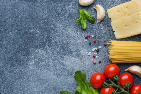 Raw Italian pasta spaghetti and cooking ingredients cherry tomatoes Cheese greens. Italian food dark stone background. Top view with copy space.