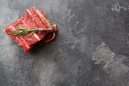 Fresh raw piece of beef rib with meat on a dark concrete background with copy space Reklamní fotografie
