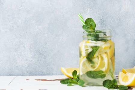 Detox water for healthy lifestyle. Fresh water in jar with lemon, cucumber and mint on wooden table Copy space