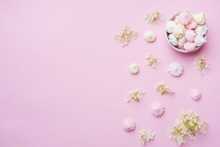 Colored small meringues on a pink background. Flat lay concept. Copy space
