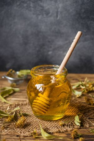A jar of liquid honey from Linden flowers and a stick with honey on a dark background Copy space