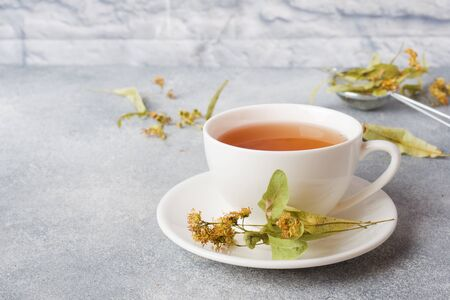 Cup of green tea and flowers linden on grey background. Copy space