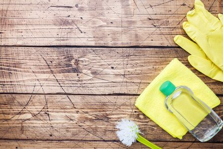 Bottles with detergents, brushes and sponges on wooden background. Colorful cleaning products. Home cleaning concept. Top view, copy space 写真素材