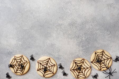 Homemade cookies for Halloween. Cookies with chocolate web and spiders Copy space. Stock Photo