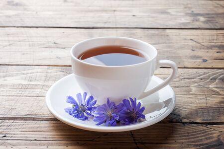 Tasse mit Zichoriengetränk und blauen Zichorienblumen auf Holztisch Platz kopieren