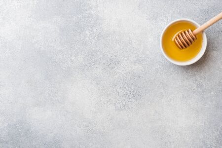 Liquid honey and honey stick on a gray background copy space