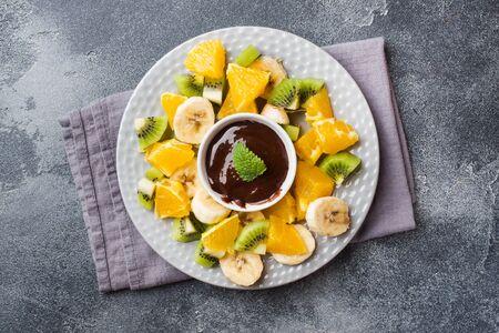 Chocolate fondue with fruit on a dark concrete background. concept summer party Copy space Foto de archivo