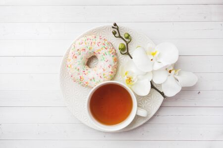 Cup of tea and donuts, white orchid on white table with copy space. Flat lay, top view Reklamní fotografie