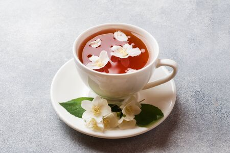 Cup of tea with Jasmine flowers on a gray table with copy space
