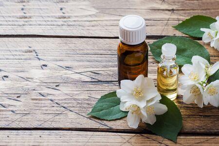 Oil of jasmine. Aromatherapy with jasmine oil. Jasmine flowers. Wooden background with copy space