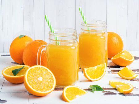 Succo d'arancia in barattoli di vetro e arance fresche su fondo rustico in legno bianco Archivio Fotografico