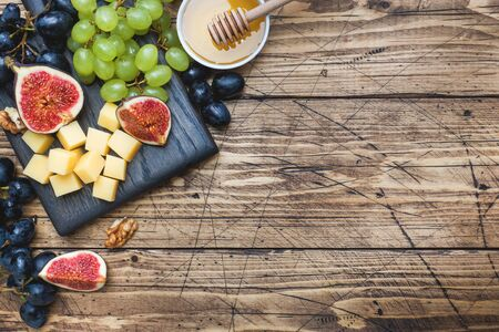 Cheese cubes, fresh fruit figs grapes Honey walnut on wooden chopping Board. Copy space Фото со стока - 132284844