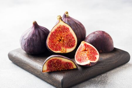 Ripe figs whole and cut on a wooden cutting Board. Selective focus.Copy space Фото со стока - 132284842