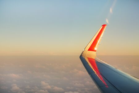 View the wing of a passenger plane and the sunset sky from the window of a flying aircraft Фото со стока