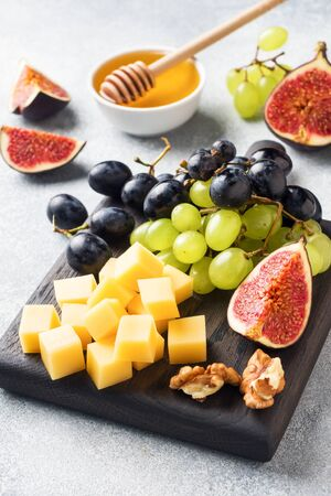 Cheese cubes, fresh fruit figs grapes Honey walnut on wooden chopping Board. Selective focus. Close up Фото со стока - 132284920