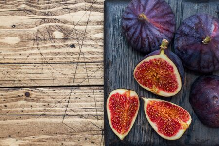Ripe figs whole and cut on a wooden cutting Board. Selective focus.Copy space Фото со стока - 132284964