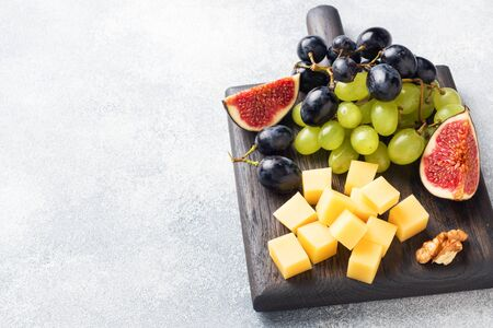 Cheese cubes, fresh fruit figs grapes Honey walnut on wooden chopping Board. Copy space Фото со стока - 132285003