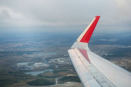 View the wing of the passenger plane and the ground from the window of the flying aircraft Фото со стока