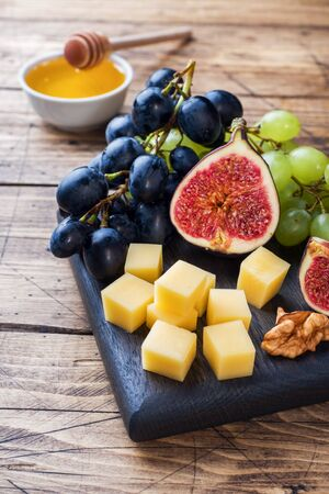 Cheese cubes, fresh fruit figs grapes Honey walnut on wooden chopping Board. Copy space Фото со стока - 132285086