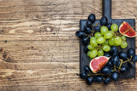 Clusters of black and green grapes Kish Mish and figs on a wooden Board. Copy space Фото со стока