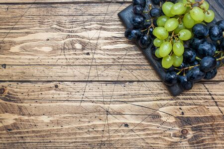Clusters of black and green grapes Kish Mish on a wooden Board. Copy space