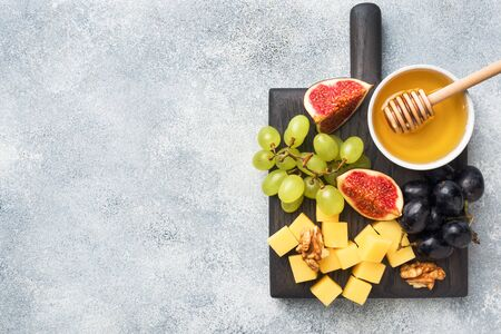Cheese cubes, fresh fruit figs grapes Honey walnut on wooden chopping Board. Copy space