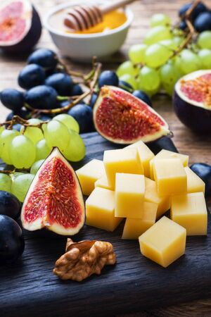 Cheese cubes, fresh fruit figs grapes Honey walnut on wooden chopping Board. Selective focus. Close up