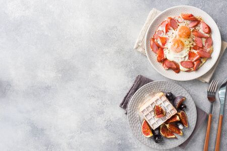 Dishes for home cooked hearty Breakfast. Fried eggs with sausages and tomatoes. Belgian fluted waffles with figs and grapes. Gray concrete background copy space