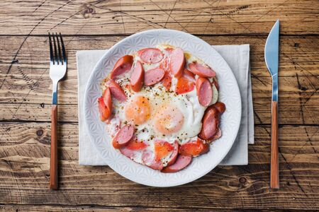 Fried eggs sausages and tomatoes on a plate on the table. Rich homemade Breakfast. Wooden background. Copy space Фото со стока - 132300442