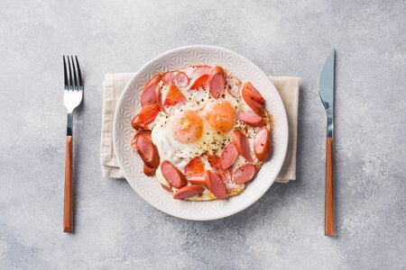 Fried eggs sausages and tomatoes on a plate on the table. Rich homemade Breakfast. Gray concrete background. Copy space