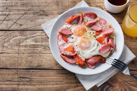 Fried eggs sausages and tomatoes on a plate on the table. Rich homemade Breakfast. Wooden background. Copy space Фото со стока