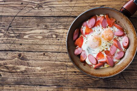 Pan with fried eggs sausages and tomatoes on the table. Rich homemade Breakfast Фото со стока - 132300503