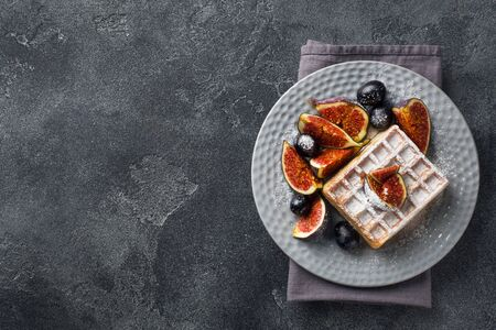 Traditional Belgian waffles with powdered sugar grapes and figs. Cozy homemade Breakfast. Gray concrete background. Copy space Фото со стока - 132300611