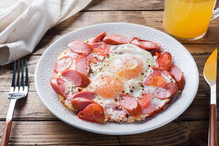 Fried eggs sausages and tomatoes on a plate on the table. Rich homemade Breakfast. Wooden background close up