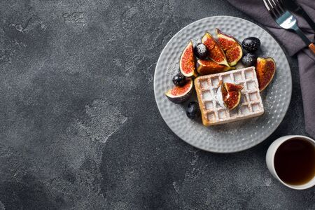 Traditional Belgian waffles with powdered sugar grapes and figs. Cozy homemade Breakfast. Gray concrete background. Copy space Фото со стока - 132300549