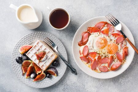 Dishes for home cooked hearty Breakfast. Fried eggs with sausages and tomatoes. Belgian fluted waffles with figs and grapes. Gray concrete background.