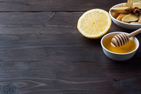 Lemon liquid honey and ginger. Ingredients for the drink is used for colds.Dark wooden background copy space Фото со стока