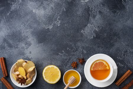 White Cup with natural herbal tea ginger lemon and honey cinnamon. Energy vitamin drink is used for colds.Dark concrete background copy space. Фото со стока