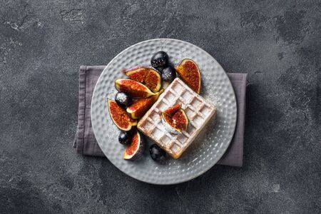 Traditional Belgian waffles with powdered sugar grapes and figs. Cozy homemade Breakfast. Gray concrete background. Copy space