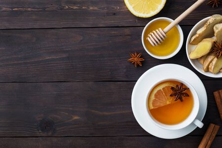 White Cup with natural herbal tea ginger lemon and honey cinnamon. Energy vitamin drink is used for colds.Dark wooden background copy space. Фото со стока