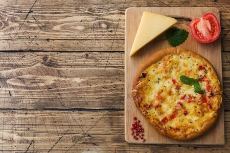 Homemade pizza tortilla with tomato and cheese on wooden background Copy space