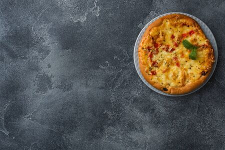 Homemade pizza tortilla with tomato and cheese on gray concrete background Copy space