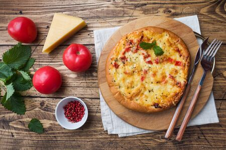 Homemade pizza tortilla with tomato and cheese on wooden background