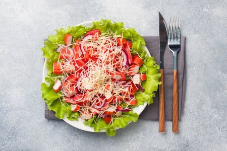 A delicious salad of crab sticks cherry tomatoes and grated cheese with onions in a serving plate