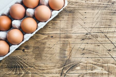 Brown raw eggs in factory packaging on rustic wooden background Copy space