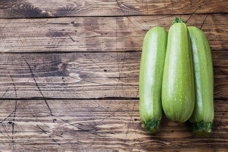 Fresh raw zucchini ready to eat on wooden background with copy space