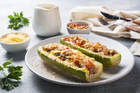 Gebackene gefüllte Zucchini-Boote mit gehackten Hühnerpilzen und Gemüse mit Käse auf einem Teller