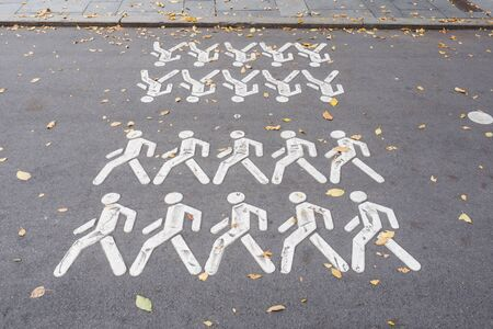 Painted symbol of a man on the asphalt. Pedestrian crossing in the Park Фото со стока